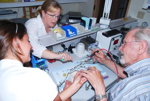 Dr Lemay enseignant la soudure pour fabriquer un appareil orthodontique aux techniciennes de laboratoire.