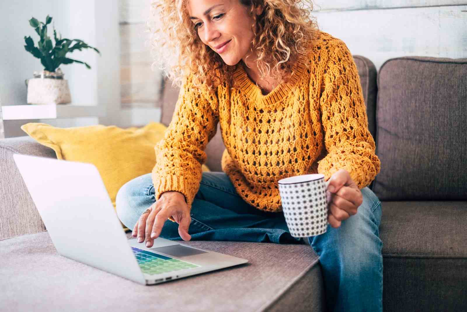 femme qui navigue en ligne sur un ordinateur portable avec une tasse dans les mains