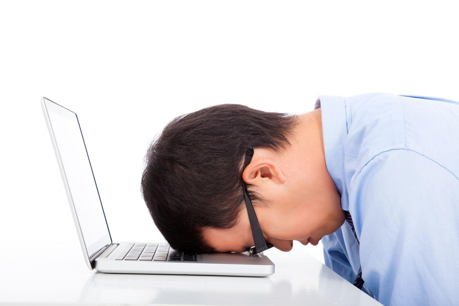 homme fatigué avec la tête sur son ordinateur portable