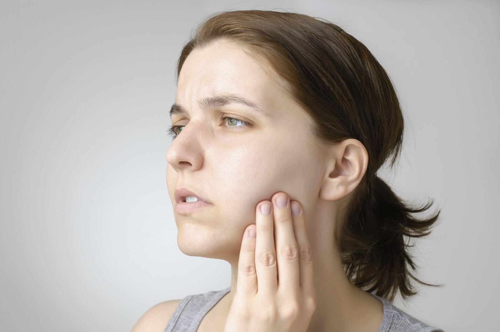 Femme qui ressent une douleur à la mâchoire