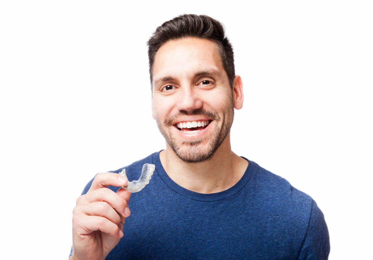 Homme souriant tenant sa plaque occlusale